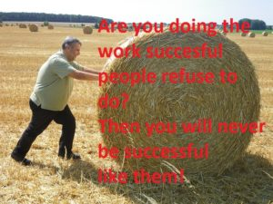 Man pushing huge straw bale by hand.